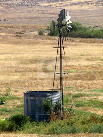 Windmill and Water Trough stock photo, Windmill and Water Trough in Field by Joseph Ligori
