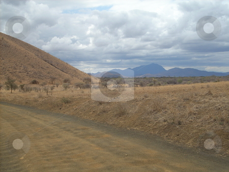 Dusty Road, Dusty Hill stock photo, Dusty road passing next to a dry dusty hill in the Tsavo National Park. by Rose Nthiwa