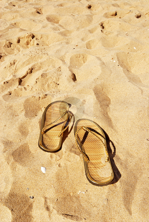 Slippers on the beach stock photo, Pair of golden slippers left in the sand with shells by Wino Evertz