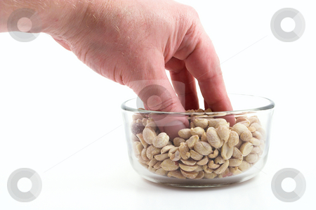 Peanuts  stock photo, Someone eating delicious peanuts from a bowl. by Robert Byron