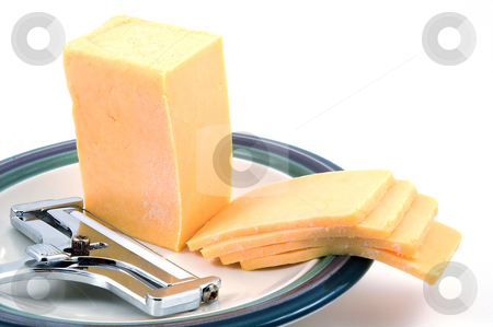 Cheese and Slicer stock photo, A hunk of delicious sharp cheddar and a cheese slicer. by Robert Byron
