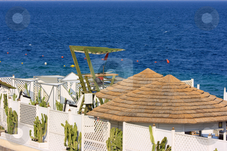 Fancy beach and lifeguard tower stock photo, Fancy beach with straw roofs and green lifeguard tower by Natalia Macheda