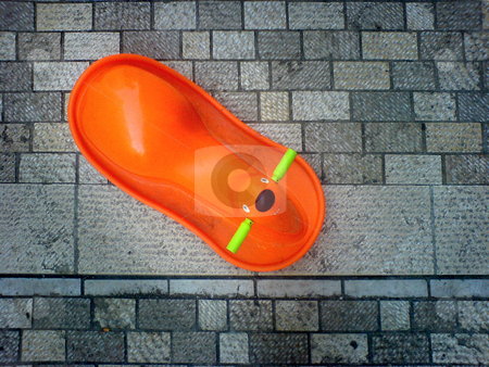 Orange rocker stock photo, An orange rocker on a cobblestone pavement by Heiko Riemann