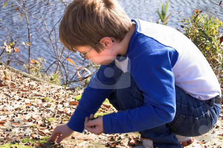 Boy Playing stock photo, A young boy playing by a lake. by Robert Byron