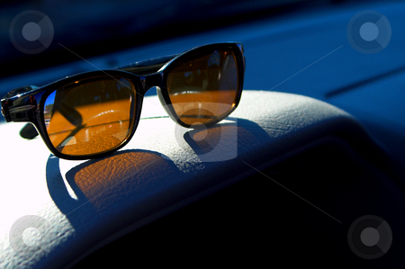 Sunglasses stock photo, A pair of sunglasses on a car dashboard. by Robert Byron