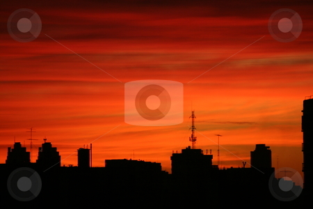 City at dawn stock photo, Silhouette of buildings in front of an orange sky at dawn by Johannes Reschl