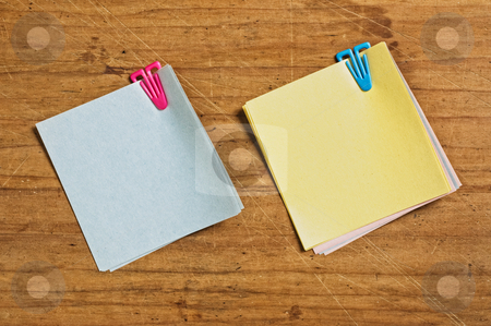 Two Post it with plastic clip  stock photo, Two Post it with plastic clip on wooden board. by Pablo Caridad