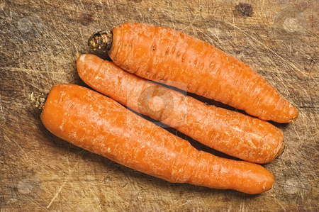 Three carrots on a cutting table. stock photo, Three carrots on a cutting table. by Pablo Caridad