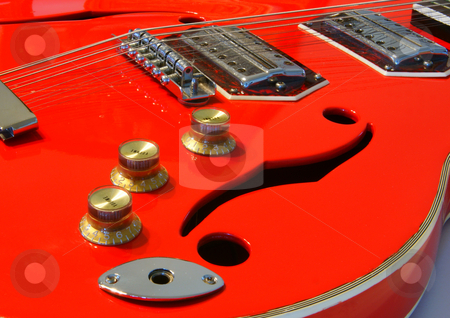 Red guitar stock photo, A red electric acoustic guitar closeup with sound holes by Sam Sapp