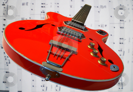 Red guitar stock photo, A red 12 string guitar on a music background by Sam Sapp