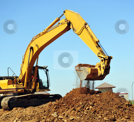 Excavator And Dirt stock photo, A large yellow excavator moving a large pile of dirt with debris falling from the bucket. by Lynn Bendickson