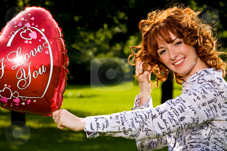 Woman with i love you balloon stock photo, Red-haired lovely young woman holding red balloon in shape of heart outdoors by Vitaly Sokolovskiy