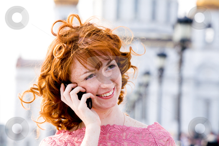 Young woman talking on mobile phone stock photo, Smiling red-haired young woman talking on mobile phone outdoors by Vitaly Sokolovskiy