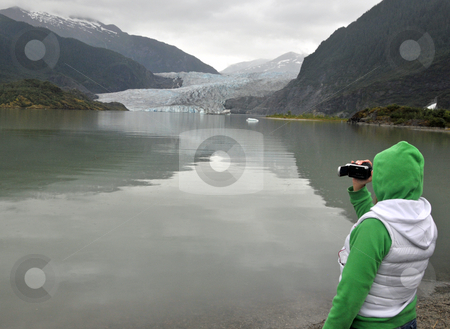 Rainy Day at the Glacier stock photo, A woman uses her video camera during a rainy day visit to a glacier by Jeff Clow