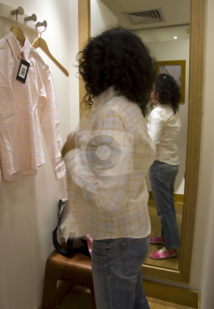 Young woman shopping ant trying a shirt stock photo, Young woman shopping ant trying a shirt and look to the mirror by Paulo Resende