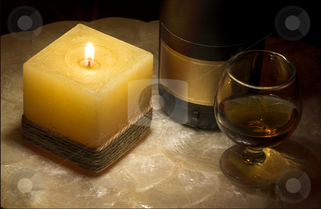Cognac and Candlelight stock photo, Cognac (wine, champagne, brandy) bottle with glass and soft light glow from a lit candle by A Cotton Photo