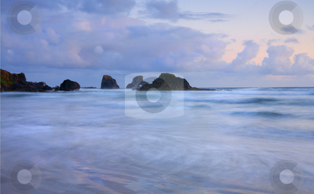 Against the Tides stock photo, Indian Beach covered by high tide as the last light of dusk adds some pastel color to the sky. For movie fans the rocky headland served as the backdrop for the Pirate ship sailing in Goonies by Mike Dawson