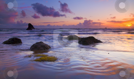 Sunset Ripples stock photo, Ripples formed in the sand by the ebb and flow of the tide glow and reflect the colors of the setting sun along Indian Beach on the Oregon Coast. The Tillamook Rock Lighthouse now just a beacon appears on the horizon. by Mike Dawson