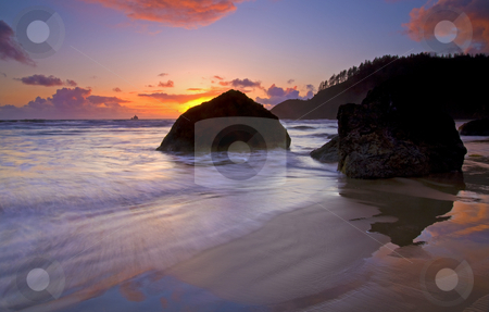 Anchoring the Beach stock photo, A colorful sunset as the tides rise over the rippled sand of Indian Beach. The boulders seemingly anchoring the sand and sea. by Mike Dawson