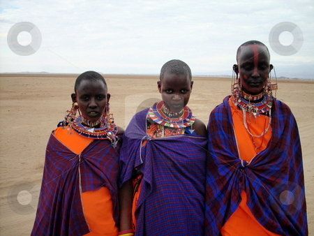 Young Masai Girls stock photo, Beautiful young Masai girls with red ocre on their faces dressed in their bright colored traditional clothes and colorful beads by Rose Nthiwa