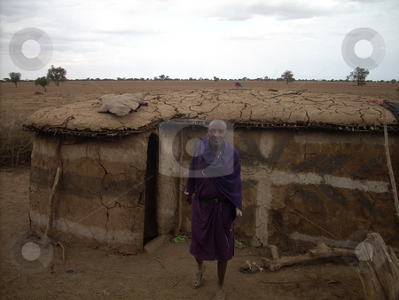 Masai Man standing in front of his hut stock photo, A Masai elder standing in front of his traditional hut which is made of mud and cowdung. by Rose Nthiwa