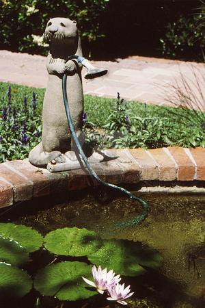 Garden Helper stock photo, Critter statue at lily pond by Joseph Ligori