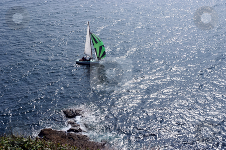 Downwind stock photo, Small sailboat just off the coast taking part in race by Paul Phillips