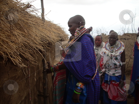 Masai Woman in front of hut stock photo, Masai woman holds a stick in front of a hut by Rose Nthiwa