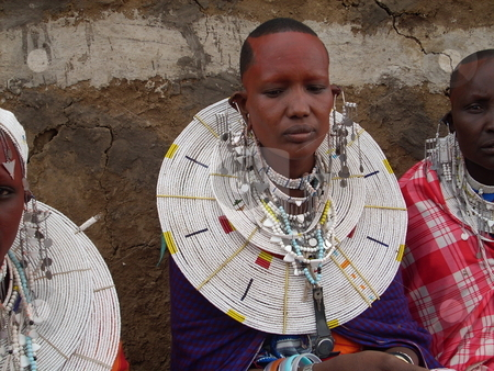 Tanzanian Masai Woman with red ocre on face stock photo, A Masai Woman from Tanzania with red ocre on her face wearing white beaded necklaces by Rose Nthiwa