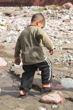 Boy playing on the riverbank stock photo, Small boy playing on the riverbank in Morocco by stomping his foot in the mud by Szilard Kun