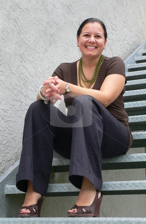 Sitting on the Steps stock photo, Attractive woman sitting on exterior steel stairs by Perry Correll