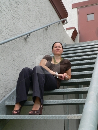 Relaxing on the Steps stock photo, Attractive woman sitting on exterior steel stairs by Perry Correll