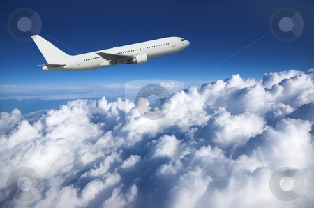 Large airliner along clouds stock photo, Large airplane climbing along cloud top against a deep blue sky by Pierre Landry