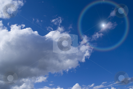 Sun stock photo, The sun is shining through the clouds in a deep blue sky. by Serge VILLA