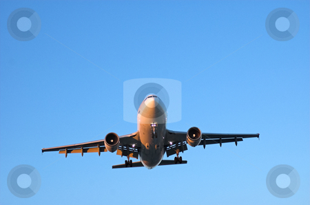 Wide body airliner in blue sky stock photo, Big jet airplane approaching for landing in clear blue skies by Pierre Landry