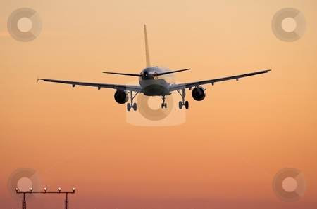 Airliner landing at sunset stock photo, Rear view of jet airplane over the approach lights at major airport by Pierre Landry