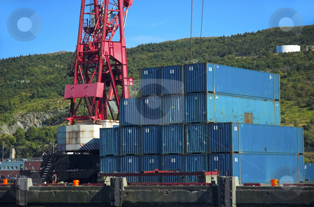 Shipping containers stock photo, Blue shipping containers beside red crane by Pierre Landry