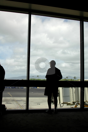 Man looking out at Honolulu from inside the terminal. Hawaii stock photo, An ailrline passenger looks out a big window to view Honolulu in the distance upon arrival in Hawaii. by Janie Mertz