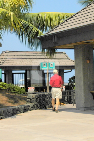 Man walking to Gate in Tropical outdoor Airport. stock photo, A senior is walking to an outdoor gate in Hilo Airport, Hawaii. by Janie Mertz