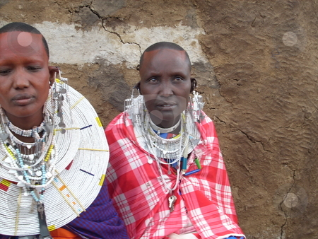 Two Masai women seated side by side stock photo, Two Masai Women seated next to each other infront of Manyatta wall. by Rose Nthiwa