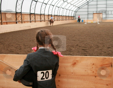 Watching the Competition stock photo, A young equestrian with riding helmet under her arm, watches the competition in the horse show ring by Tom and Beth Pulsipher