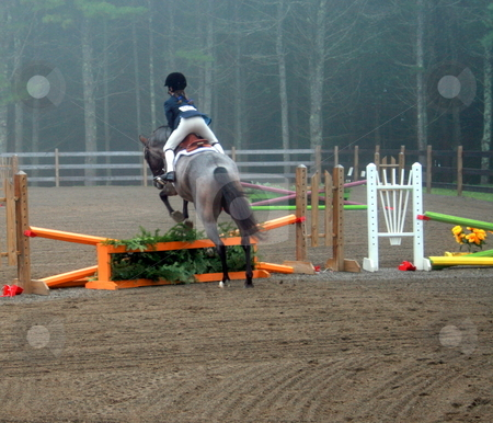 Horse Jumping stock photo, A young equestrian and horse jump over the orange gate by Tom and Beth Pulsipher