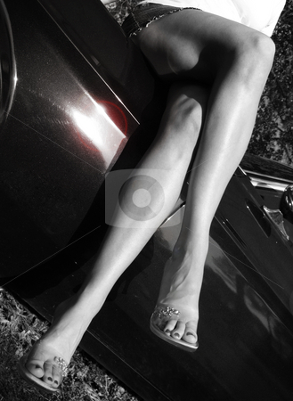 Long Legs stock photo, Long legs atop a vintage car in black and white with colorized lens flare by Anita Peppers