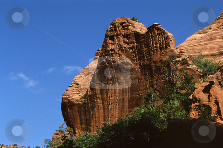 Red Rock cliff face stock photo, Cliff face of red rock againt an almost cloudless deep blue sky by Joseph Ligori
