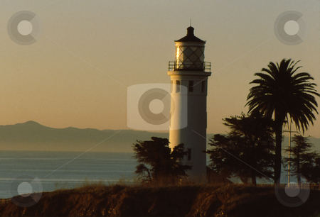 Lighthouse at sunset stock photo, Lighthouse at point at sunset by Joseph Ligori