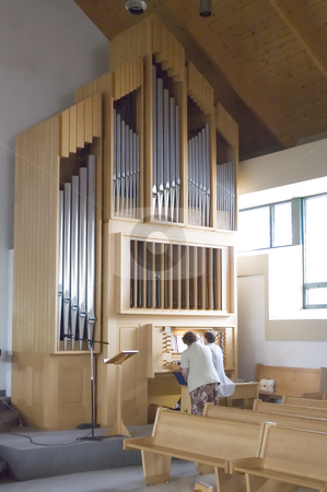 Pipe Organ stock photo, Two aged ladies playing a pipe organ at a catholic church by Vlad Podkhlebnik