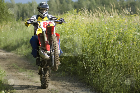 Motocross rider stock photo, A motocross rider making wheelies on his bike by Vlad Podkhlebnik