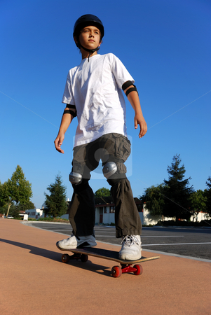 Boy on a Skateboard stock photo, Boy on a Skateboard Against Blue Sky Looking in the Sun by Denis Radovanovic