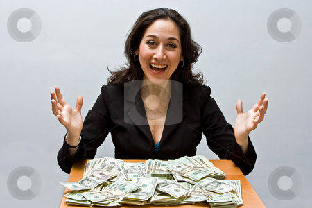 Successful finance stock photo, Happy business woman sitting at a table covered with stacks of money isolated on a white background by Paul Hakimata