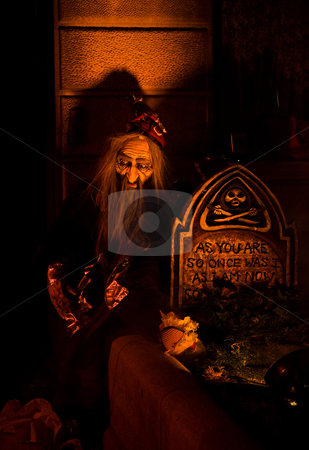 Graveyard shift stock photo, Old bearded man (puppet) sitting at a graveyard at a lit up tomb; a Halloween set-up by Paul Hakimata